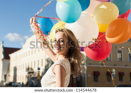 Happy young woman with colorful latex balloons keeping her dress, urban scene, outdoors - stock photo