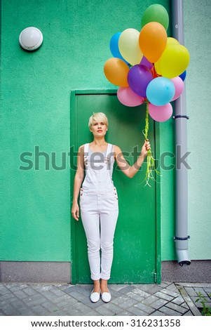 Happy young woman with colorful latex balloons on green background, outdoor - stock photo