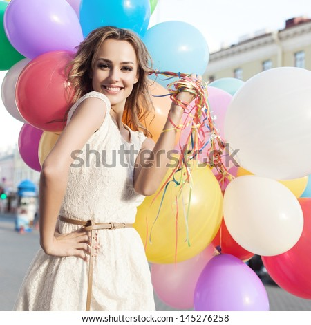 Happy young woman with colorful latex balloons, outdoors - stock photo