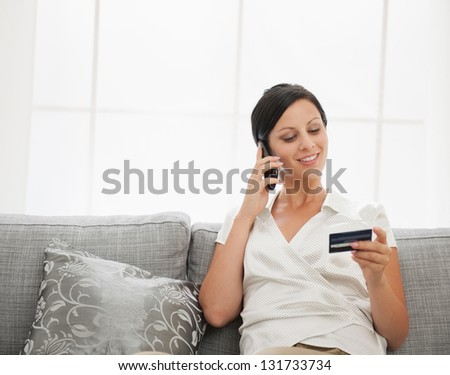 Happy young woman with credit card sitting on sofa and talking mobile phone - stock photo