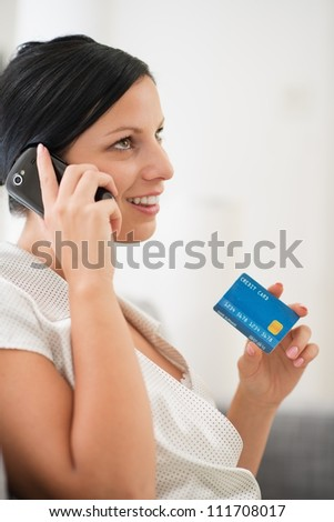 Happy young woman with credit card speaking mobile
