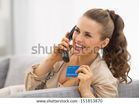 Happy young woman with credit card talking phone - stock photo