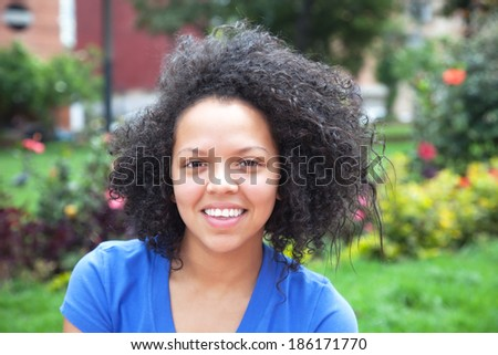 Happy young woman with curly hair in a park - stock photo