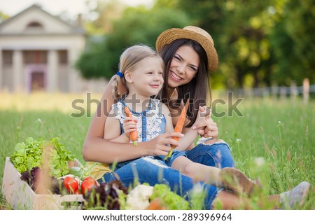 Happy young woman with daughter eating vegetables from crate of freshly harvested vegetables