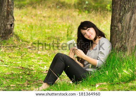 Happy young woman with digital tablet sitting on grass in park