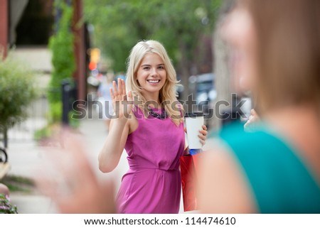 Happy young woman with disposable coffee cup waving to female friend - stock photo
