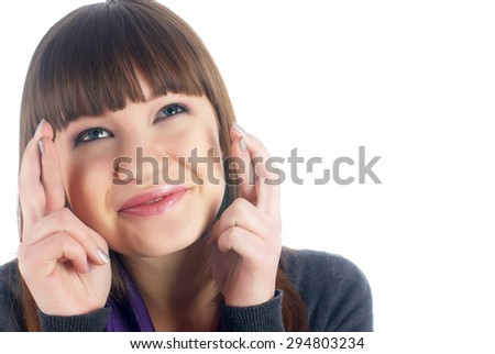 Happy young woman with fingers crossed on white. - stock photo