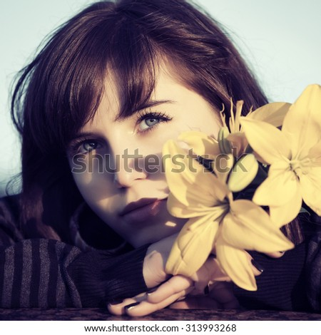 Happy young woman with flowers daydreaming outdoor - stock photo