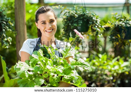 happy young woman with flowers in nursery - stock photo