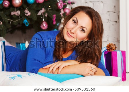 Happy young woman with gift box near christmas tree. X-mas or New Year tree concept.