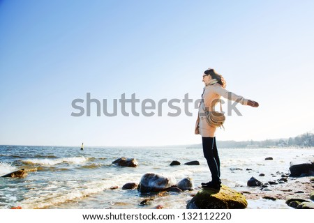 Happy young woman with hands up during a relaxing walk on the beach in a sunny day - stock photo