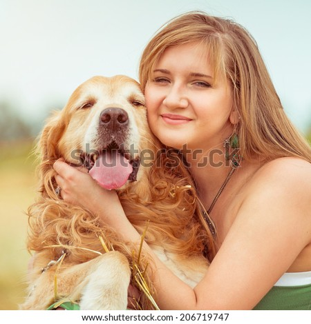 happy young woman with her dog golden retriever in rural areas in summer close-up