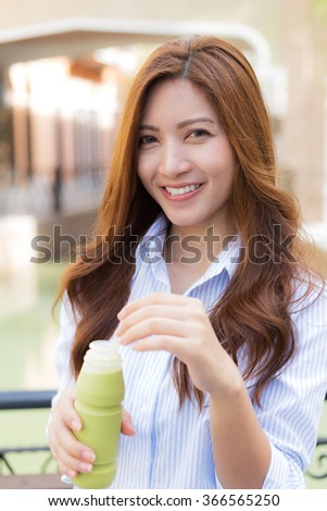 Happy young woman with ice green tea in her hand
