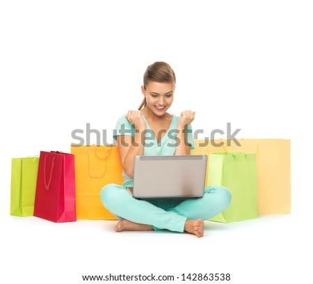 happy young woman with laptop and shopping bags - stock photo
