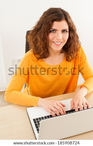 Happy young woman with laptop at home looking at camera - stock photo