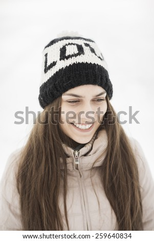 """happy young woman with """"love"""" hat on the white snow background - stock photo"""