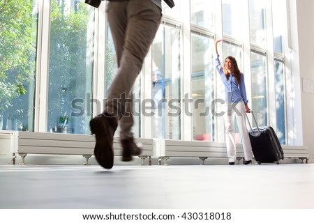 Happy young woman with luggage waving to her boyfriend. Man running towards female partner at airport. She is with luggage at departure area. - stock photo