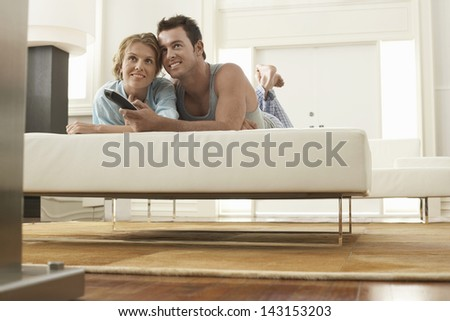 Happy young woman with man holding remote control in bed