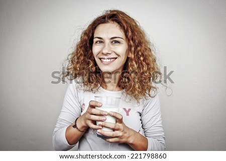 happy young woman with milk over grey background - stock photo