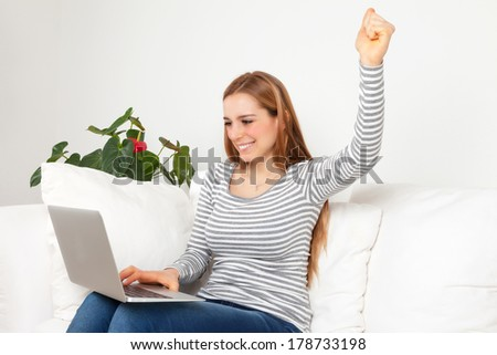 Happy young woman with notebook on a sofa - stock photo