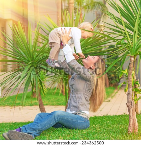 Happy young woman with pleasure playing outdoors with her cute little blond daughter, mother lifting up baby girl, having fun in the garden in sunny day, love and enjoyment concept - stock photo