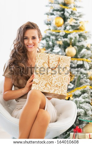 Happy young woman with shopping bag near christmas tree - stock photo
