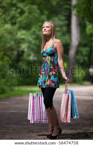 Happy young woman with shopping bags goes home after successful shopping. Outdoors. - stock photo