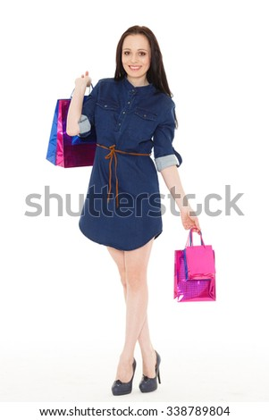 Happy young woman with shopping bags on a white background.