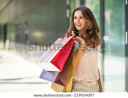 Happy young woman with shopping bags on the mall alley looking on copy space