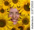 Happy young woman with sunflowers - stock photo