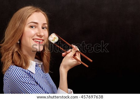 happy young woman with sushi on black background with copyspace - stock photo