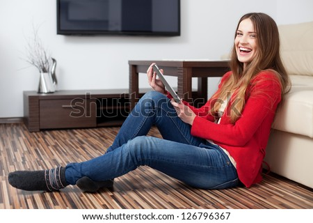 Happy young woman with tablet in living room