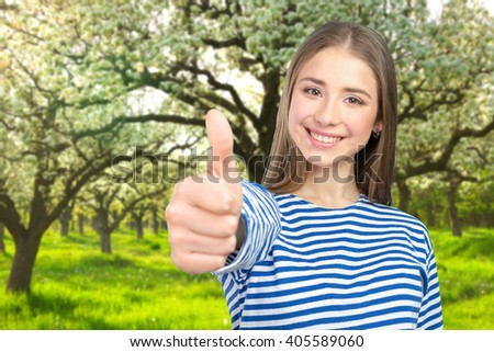 Happy young woman with thumbs up - stock photo