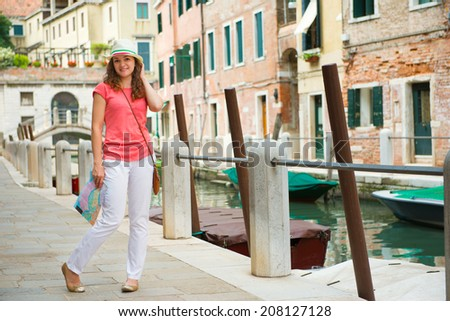 Happy young woman with tourist map in Venice