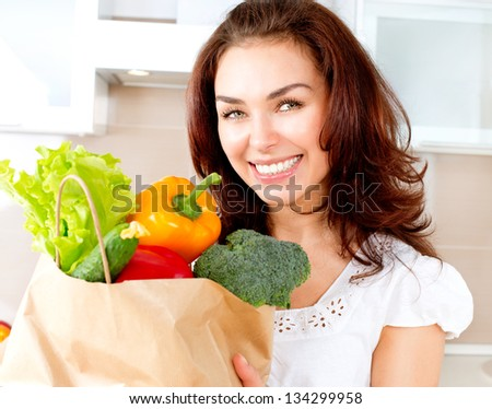 Happy Young Woman with vegetables in shopping bag . Beauty Girl in the kitchen Cooking healthy Food. Diet Concept - stock photo
