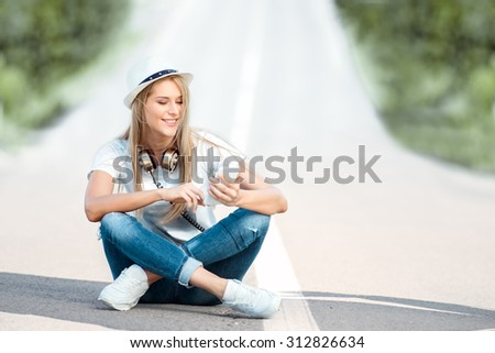 Happy young woman with vintage music headphones around her neck, surfing internet on a smartphone and sitting on a separating strip against road background. - stock photo