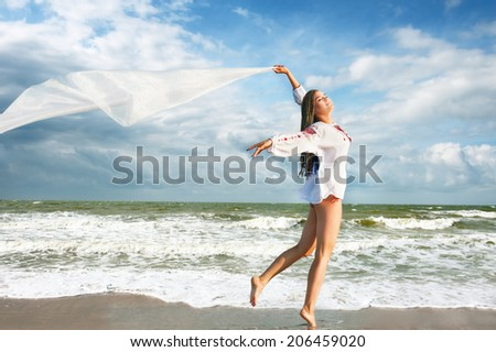 Happy young woman with white fabric at the beach. Freedom concept - stock photo