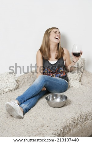Happy young woman with wine glass sitting on sofa - stock photo