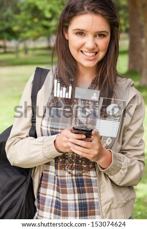 Happy young woman working on her futuristic smartphone in bright park - stock photo