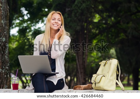 Happy young woman working on laptop computer, talking on phone in the same time in park - stock photo