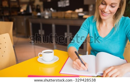 Happy young woman writing on book at table in cafe - stock photo