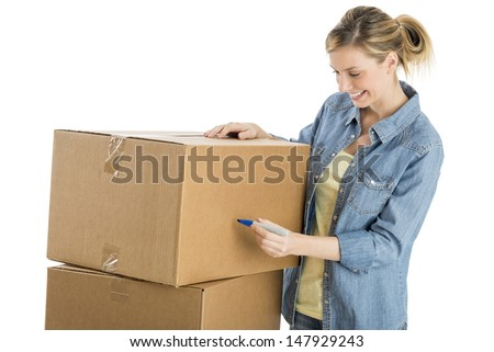 Happy young woman writing on cardboard boxes isolated over white background