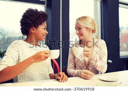 happy young women drinking tea or coffee at cafe - stock photo