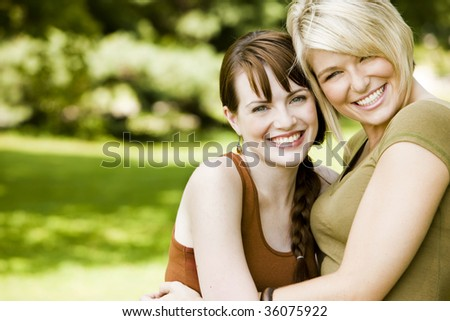 Happy young women embracing each other in the park - stock photo