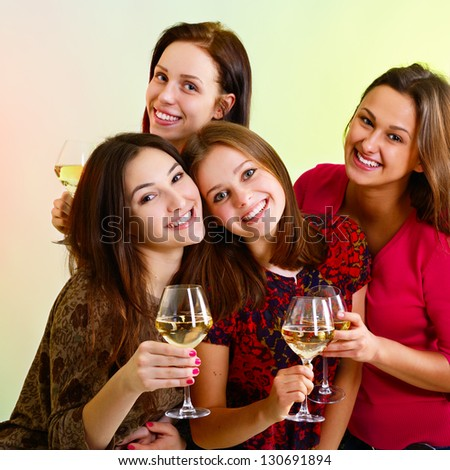 Happy young women friends touching the glasses with each other on party and have fun - stock photo