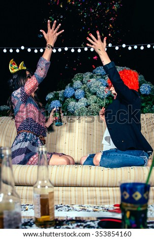 Happy young women friends with costumes throwing colorful confetti to the air in a outdoors party. Friendship and celebrations concept. - stock photo