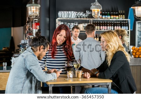Happy young women looking at male friend using mobile phone at table in bar - stock photo