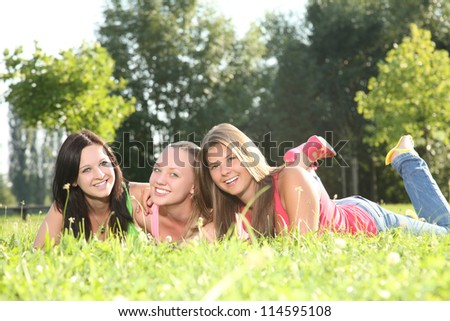 happy young women lying in the grass - stock photo