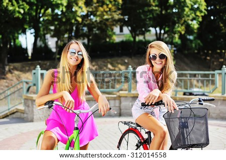 Happy young women on a bicycles in summertime
