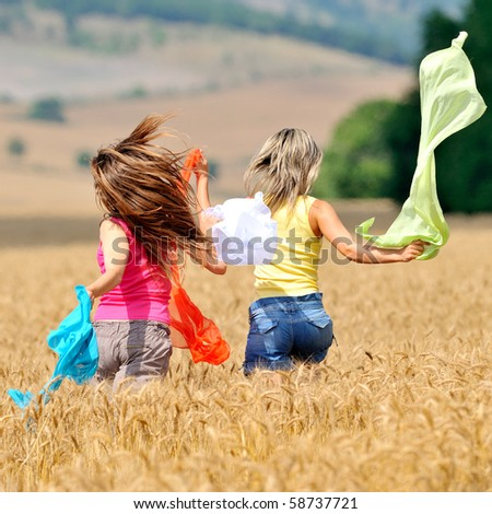 happy young women on field in summer - stock photo